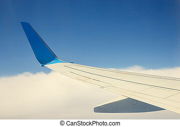 Wing of an airplane flying above the clouds on blue sky...