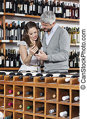 Couple With Wine Bottle Standing At Rack - Smiling couple...