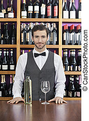 Confident Bartender With White Wine Standing At Counter -...