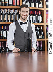 Confident Bartender With Wine Bottle Standing At Counter -...