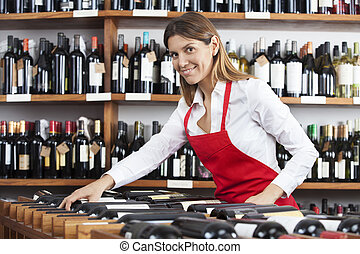 Portrait Of Saleswoman Arranging Wine Bottles In Rack -...