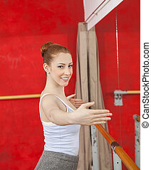 Portrait Of Smiling Ballet Dancer Performing In Studio -...