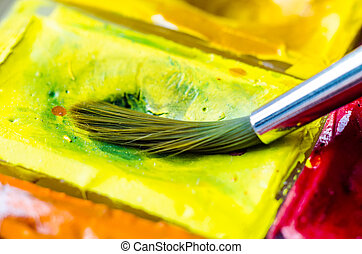 paint brush with watercolor paints macro
