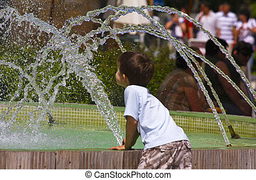 Kid playing with water fountain - Young boy playing in the...