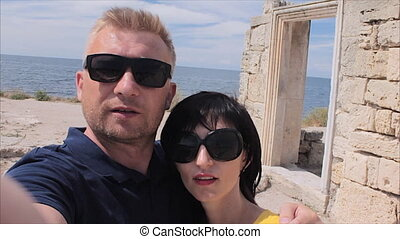 Attractive Happy Couple Taking Selfie on the ruins of the ancient city and sea beach background