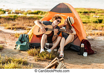 Man playing guitar and sitting at the camping tent