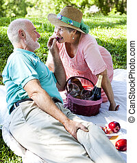 Romatic Senior Picnic - Grapes - Romantic senior couple on a...