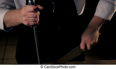 Midsection of Male Chef Sharpening Knife In Commercial...