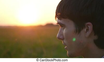 young man wears headphones on field at sunset and runs away to the sun