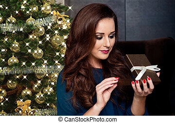 young woman opening a gift box.