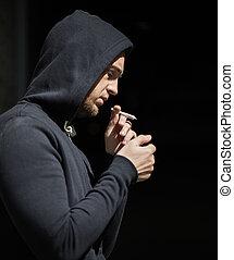 close up of addict lighting up marijuana joint - drug use,...