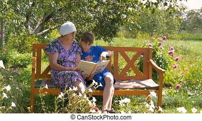 Grandson reading a book to his grandmother. - Grandson...
