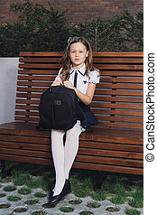 schoolgirl in uniform waiting for the bus to school