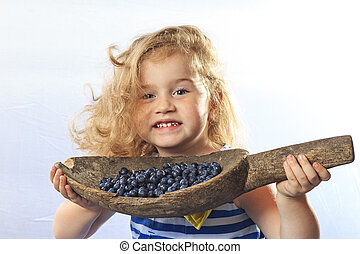 little girl holding a bucket of berries blueberries - The...