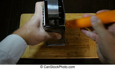 Chef using a grater for carrots. - Chef using a grater for...