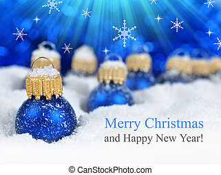 Christmas greeting card with blue decorations in snow.