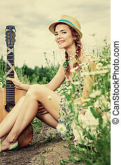 rural scene - Beautiful romantic girl with a guitar on a...