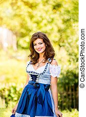 Beautiful young woman in traditional bavarian dress in park...