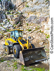 Yellow front end loader machine scooping up big stones in a...