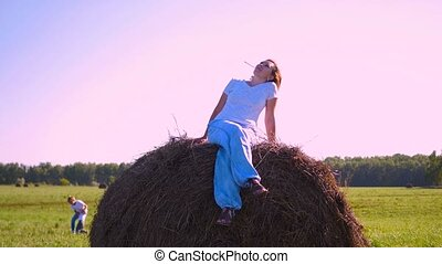 girl resting on a haystack at sunset