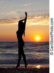 Silhouette girls by the sea at sunset