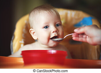 mother feeding baby boy with a spoon - mother feeding her...