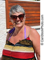 A mature woman wearing sunglasses while on vacation during...