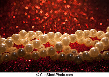 Close up of white pearls on a red glitter background.
