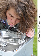 Teenager drinks from a drinking fountain - A young white...