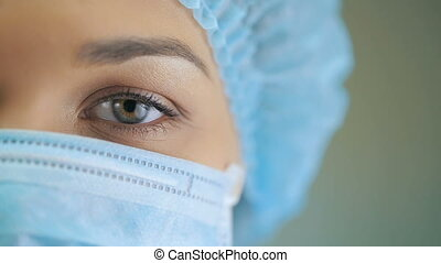 Eye of a Doctor at surgical mask - Woman wearing surgical...