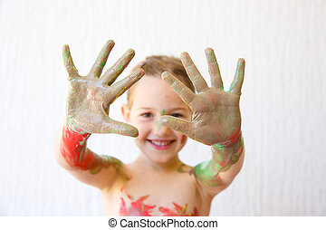 Little girl showing her hands, covered in finger paint after...