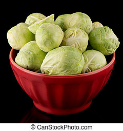 Fresh brussels sprouts on red ceramic bowl isolated on black...