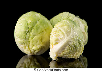 Fresh brussels sprouts isolated on black background