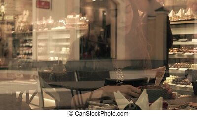 Beautiful brunette girl drinking hot chocolate in pastry shop. View through window from outside. 4K video