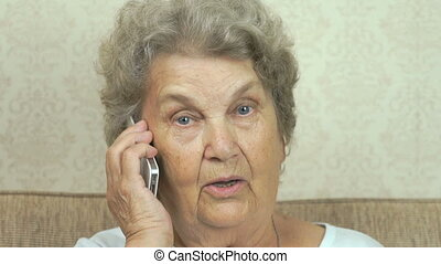 Old woman talking smartphone sitting on the sofa