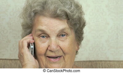 Old woman talks on smartphone to doctor at home