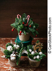 Christmas floral wreath decoration with baubles, red bow, holly and winter greenery over oak background.