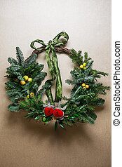 Christmas floral wreath decoration with baubles, red bow, holly and winter greenery over kraft background.