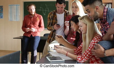 Students play smart phone video games sitting desk classroom...