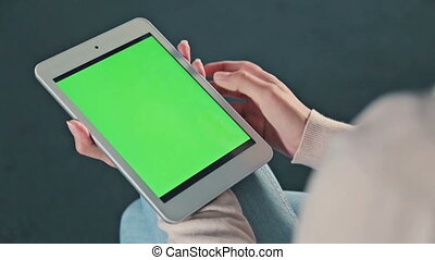 Woman using tablet with green screen