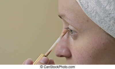 Young, pretty woman applying concealer on her eyelid in...