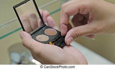 Woman is brushing eye shadow palette cosmetic in bathroom of...
