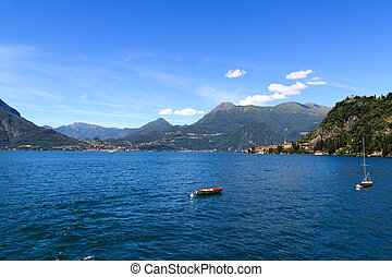 View towards Lake Como with boats and village Varenna with...