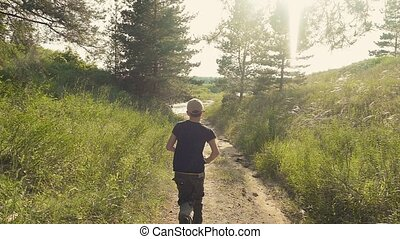 boy running along the road in the slow motion video - sunny...