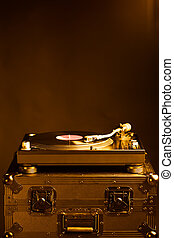 professional dj turntable on flight case, dark background,...