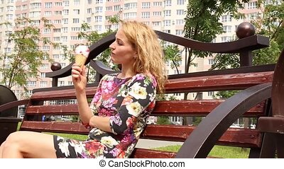Pretty happy woman sitting on a bench in a city park and eating ice cream
