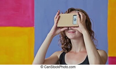 Young curly woman using Virtual Reality Glasses. Google...