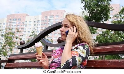 Pretty happy woman sitting on a bench in a city park, eating ice cream. Talking on the modile phone and sends a message