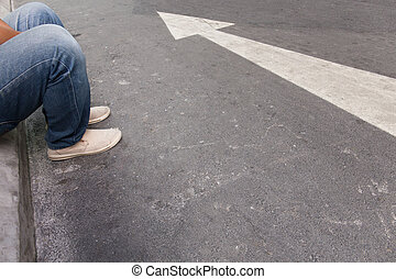 arrow - The person sitting next to the arrows on the street
