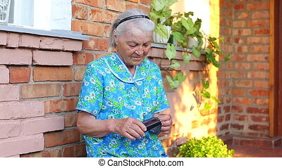 Elderly older female counts money in her wallet